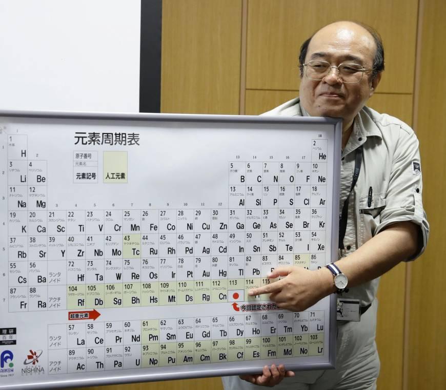 Le professeur Kosuke Morita pointant le nihonium sur la table de Mendeleïev, lors d'une conférence de presse à l'institut de recherches de Wako, dans la préfecture de Saitama.